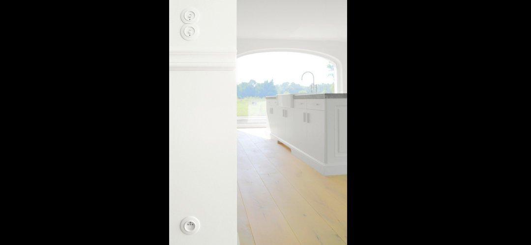 Ronde wit bakeliet schakelaars en een rond wit bakeliet stopcontact met penaarding in moderne villa in Belgie