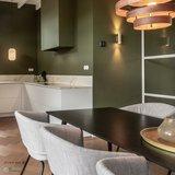 Wit bakeliet schakelmateriaal in moderne keuken met groene wanden en wit stalen deuren